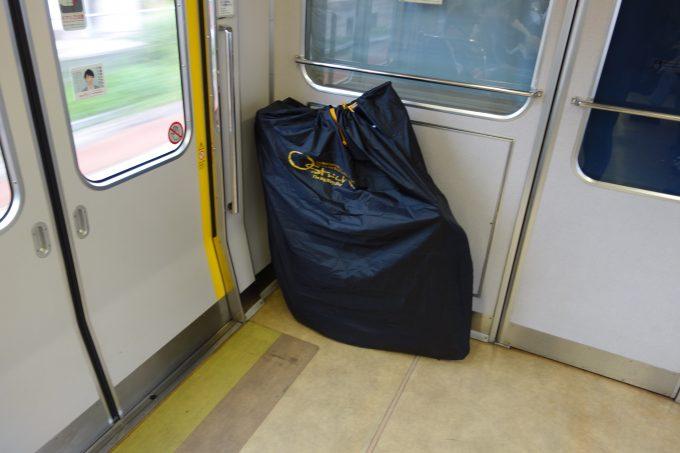 電車の車両の端に置いた輪行袋